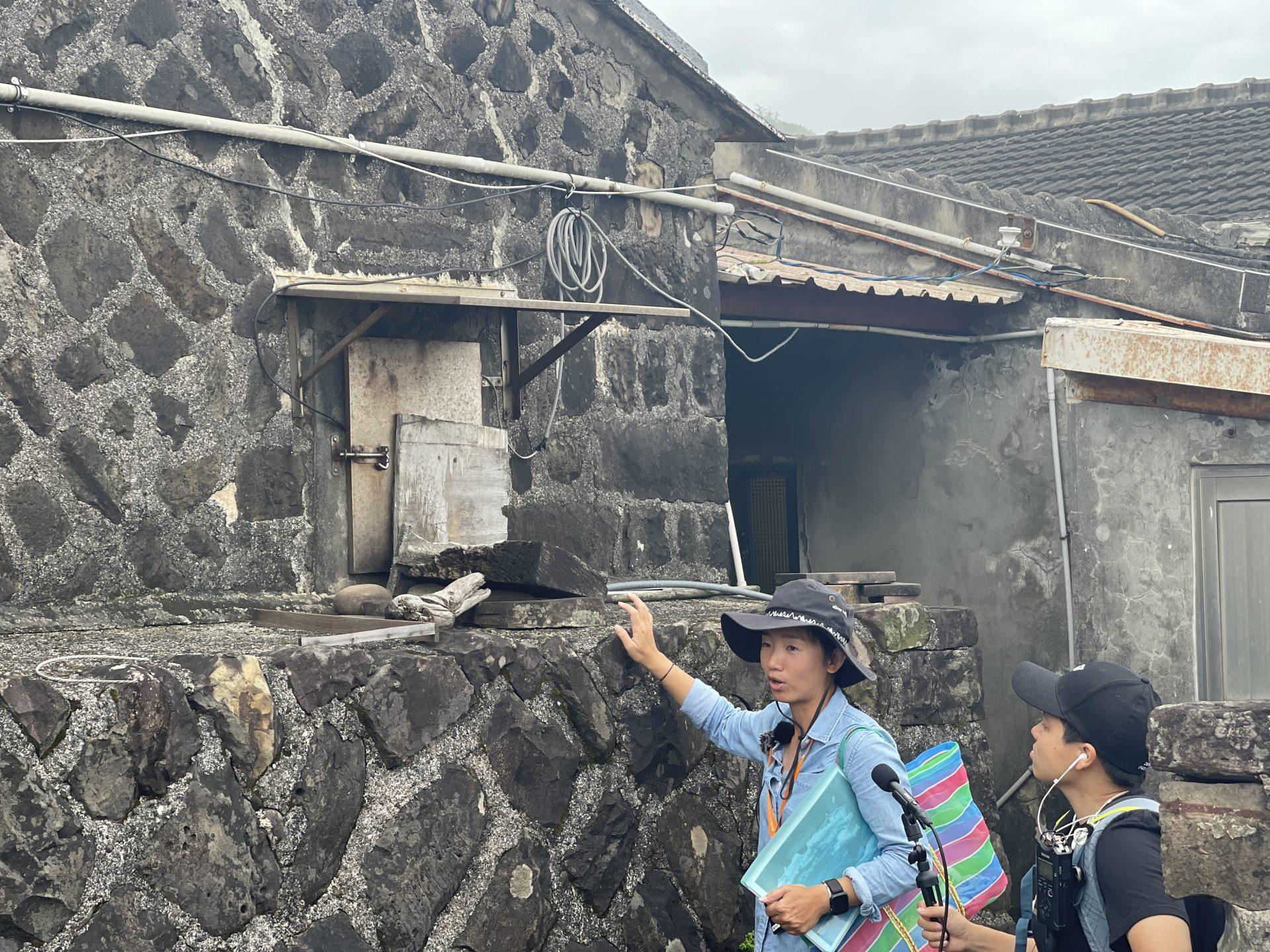導覽員講解馬崗聚落石頭屋。